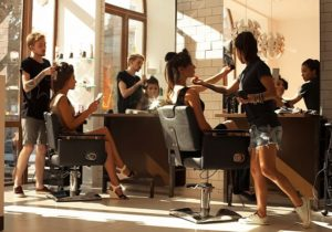Hairdressers fixing their clients' hair which shows they are at risk of developing varicose veins due to always standing and it can be treated at The Vein Institute.