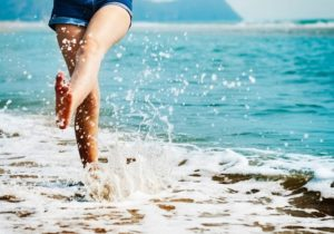 A woman on a seashore splashing the sea water. A featured image of The Vein Institute blog page and describes how varicose veins are different to normal veins.